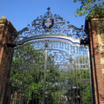 "When it was completed in 1889, Johnston Gate stood alone. The other gates and even the brick and iron fence that now encloses the Yard were still in the future. And while nothing quite as grand as its delicate ironwork and massive brick and sandstone piers had ever graced the spot before, the location of the gate has served as the Yard's main entrance since the end of the 17th century.  The gate is named for Samuel Johnston, Class of 1855, who left Harvard $10,000 for its construction. A resident of Chicago, Johnston is described in his 1886 obituary as a bachelor and a ""well-known capitalist,"" and by a fellow member of the Chicago Club as ""a short, ruddy faced bon-vivant."" A book of reminiscences by one of Johnston's neighbors describes him drinking a toast on the front steps of his house as the Chicago fire blazed nearby.  Designed by the Boston architectural firm of McKim, Mead, and White, Johnston Gate was the first example at Harvard of Colonial Revival, a style that, during the late 19th and early 20th centuries became almost standard for Harvard buildings. Built of salvaged bricks chosen for their varied texture and color, the structure also helped to popularize what has come to be known in the building trade as ""Harvard water-struck brick,"" used on most Harvard buildings since that time.  The gate bears two plaques inscribed with the earliest records of Harvard's founding, an inscription from ""New England's First Fruits"" (1643) and the records of the General Court of Massachusetts Bay establishing the College."